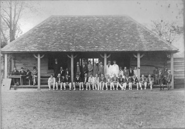 Two sets of players, umpires, spectators and scorers gather in front of the new clubhouse, taken shortly after its opening c.1930.Front row: Arthur Cutforth (second left), Harry Boatman (fifth left), Ernie Clarke (sixth left), Reg Salmon (eighth left). Maurice Kampe stands between Artur Cutforth and Harry Boatman.